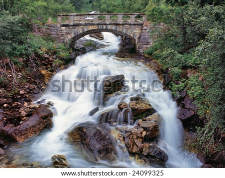 Old stone bridge over small stream water - stock photo