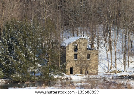 Old stone building on stream bank in winter