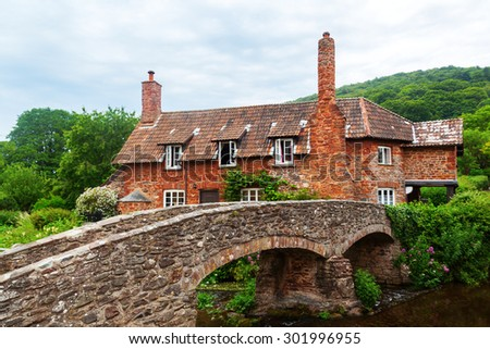 old stone cottage with packhorse bridge in Allerford, Somerset, England - stock photo