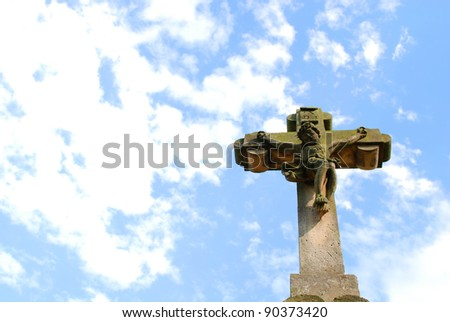Old stone cross against blue shining sky - stock photo