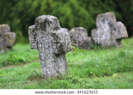 old stone cross in green grass - stock photo