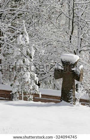 Old stone cross on the grave in the snow. Winter landscape. - stock photo