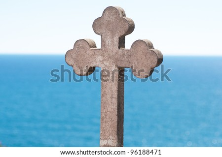 Old stone cross over blue sky and sea