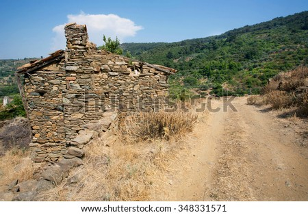 Old stone house in traditional turkish village with dirt road in mountains - stock photo