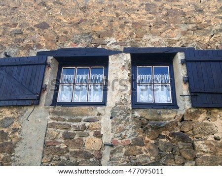 Old stone house windows in France with wooden shutters and vintage lace curtains