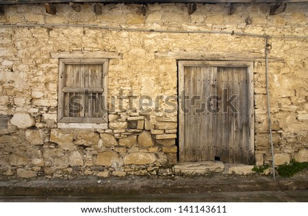 Old stone house with wooden door and window