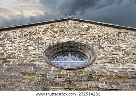 Old stone made facade of  small christian church in Italy - stock photo