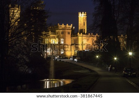 Old stone majestic illuminated castle in woods near lake with a fountain in the night. - stock photo