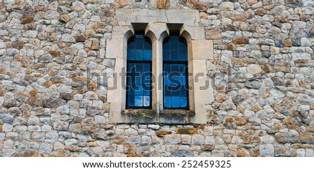 Old stone medieval wall with two windows in center - stock photo