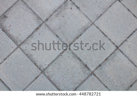 Old stone paving on the street. Concrete or cobble gray pavement slabs or stones. - stock photo