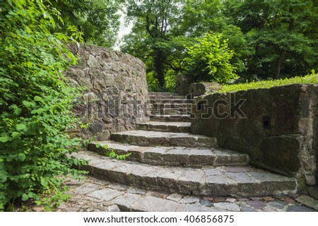 Old stone staircase and wall in a green park