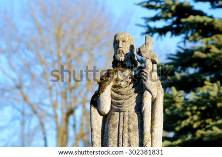 Old stone statue at the tomb of St. Peter in the old cemetery on the background of the sky in Ukraine - stock photo