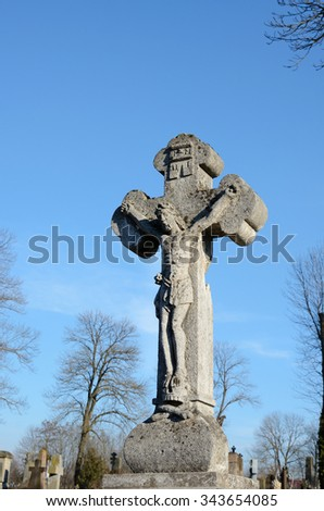 Old stone statue of Jesus crucified on the cross on the tombstone in the cemetery in Ukraine - stock photo
