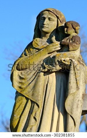 Old stone statue of the Virgin with Jesus at the grave in the old cemetery in Ukraine - stock photo