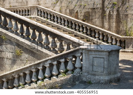Old stone steps climbing several flights with ornate carved balustrade