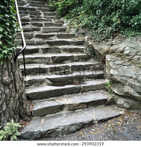 Old stone steps in green summer garden. - stock photo