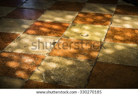 Old stone tiles glow in sunlight in a church in Venice, Italy. - stock photo