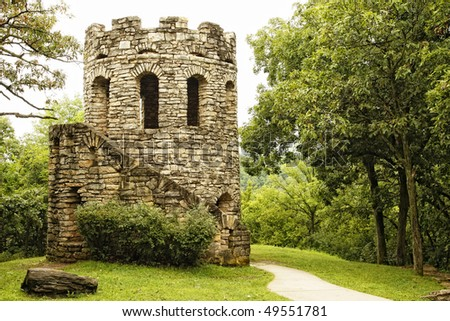 Old stone tower in tranquil setting among lush green scenery (historic landmark, Clark Tower, in Winterset, Iowa). - stock photo