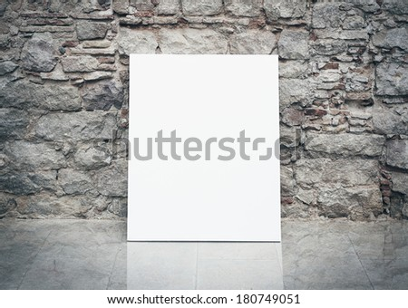 Old stone wall and blank poster - stock photo