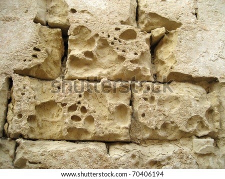 Old stone wall eroded by weather and pollution - stock photo