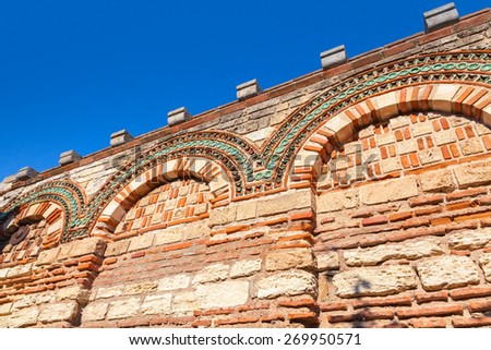 Old stone wall with ancient pattern and clear blue sky, Church in Nessebar town, Bulgaria - stock photo