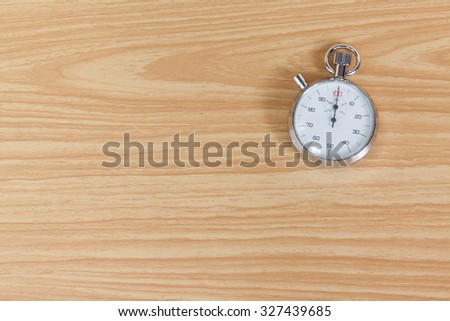 Old stopwatch on wooden table - stock photo