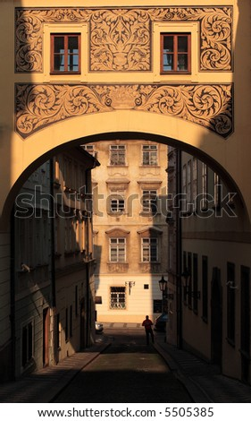 Old street in Prague with a richly decorated elevated corridor. - stock photo