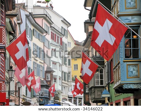 Old street in Zurich decorated with flags for the Swiss National Day - stock photo