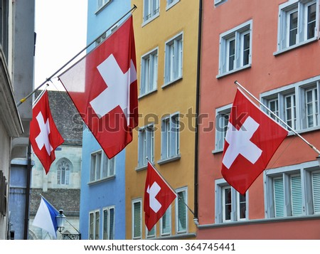 Old street in Zurich decorated with flags for the Swiss National Day, 1st of Augus - stock photo