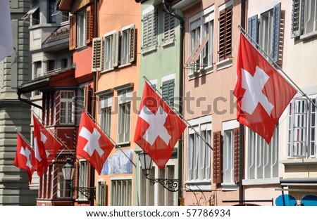 Old street in Zurich decorated with flags for the Swiss National Day, 1st of August