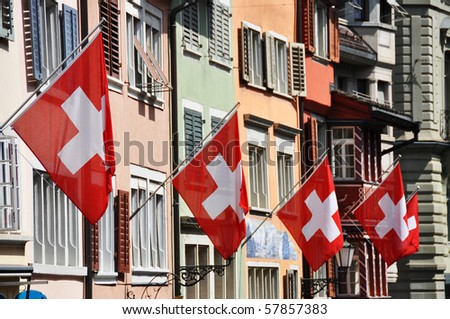 Old street in Zurich decorated with flags for the Swiss National Day, 1st of August - stock photo