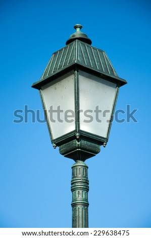 Old street lamp on blue sky background. - stock photo