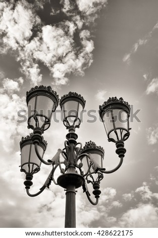 Old street lamps against the sky with clouds - stock photo