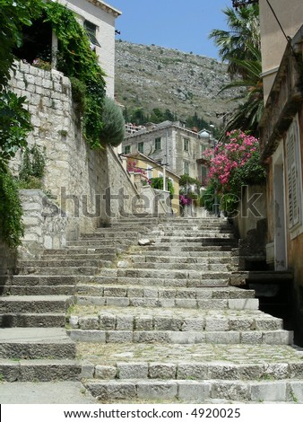 Old street of Dubrovnik with lot of flowers goes upstairs - stock photo