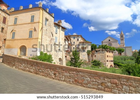 Old street with medieval buildings and distant Basilica di Santa Chiara on sunny hillside in Assisi, region of Umbria, Italy