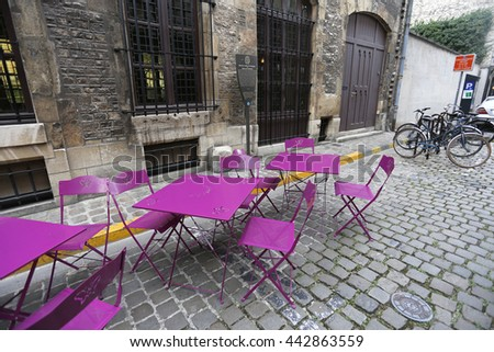 Old street with modern colorful tables and chairs in France