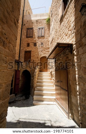 Old street with sandstone arc and wooden closed doors in downtown of Saida, Lebanon - stock photo