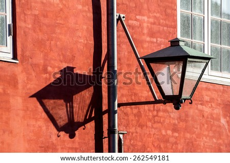 Old streetlamp on a red brick wall