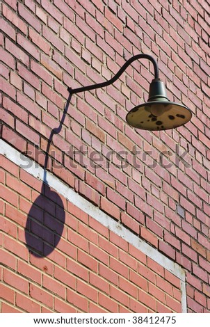 old streetlight on a brick wall during day time - stock photo