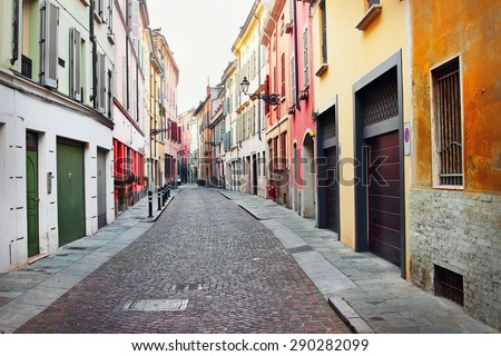 Old streets in Italian historical town, Parma, Italy. Houses painted in different colors.