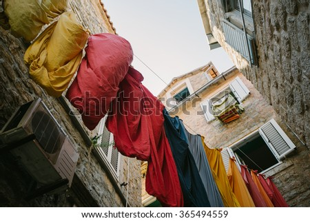 old streets of Europe and the multi-colored dry clothes in a narrow street - stock photo