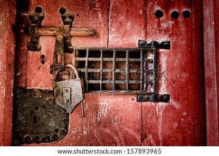 Old strong lock and cast iron latch locking hardware with speakeasy window on a medieval dungeon antique wood jail door  - stock photo