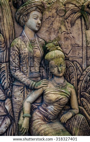 Old stucco from Thai women literature hang on the wall - stock photo