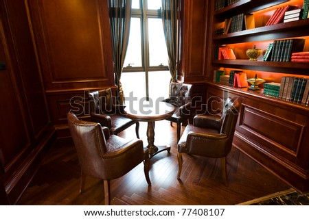Old studying room with four leather armchairs and wooden table. - stock photo