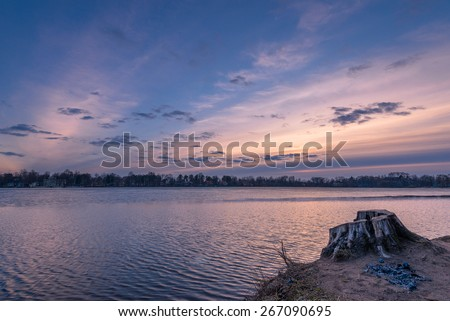 Old stump on lake coast during sunset time with cloudscape on background - stock photo