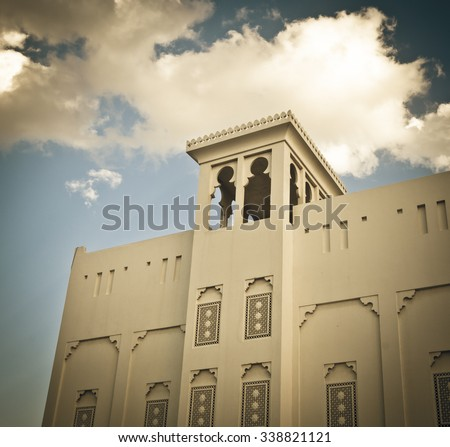 Old style arabic building with a wind tower. Ancient cooling system. - stock photo