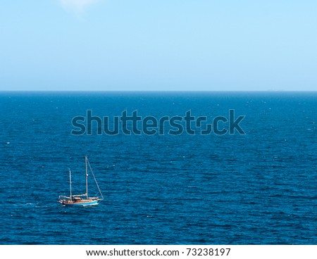 Old style boat sailing through calm ocean in a clear sunny day - stock photo