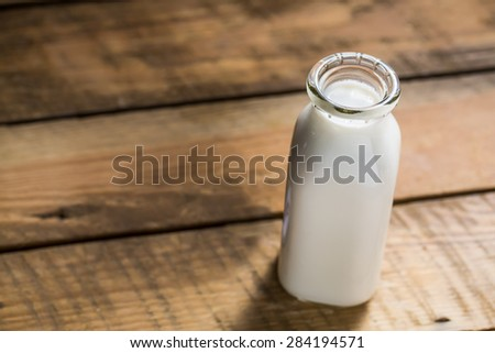 Old style bottle of milk sitting on wood table shot from slightly above with selective focus. - stock photo