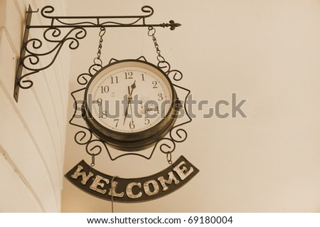 Old style hanging clock with welcome sign on wall