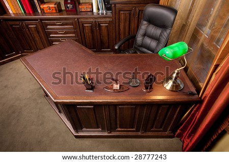Old style home office with leather armchair and green lamp - stock photo